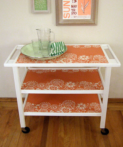 White and orange serving cart with a glass, pitcher, and plate