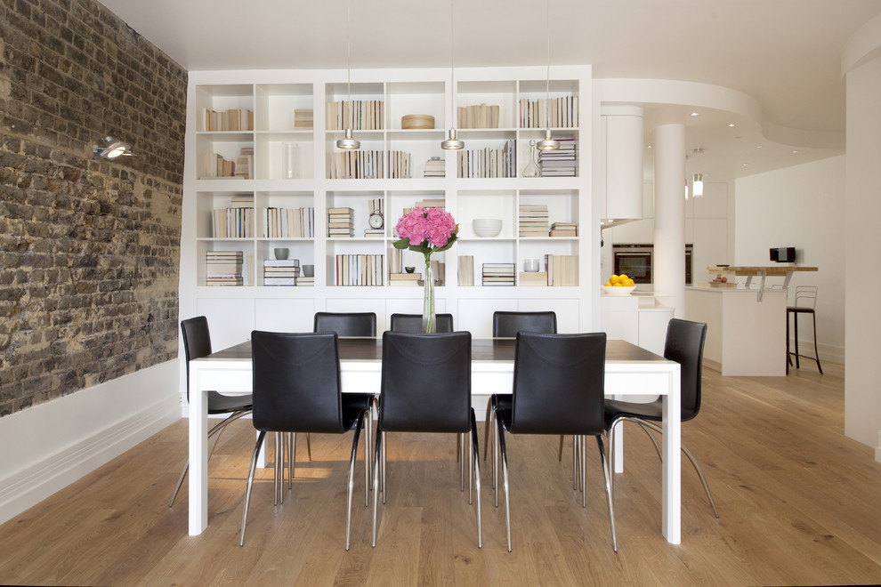 Dining room - contemporary medium tone wood floor dining room idea in London with white walls