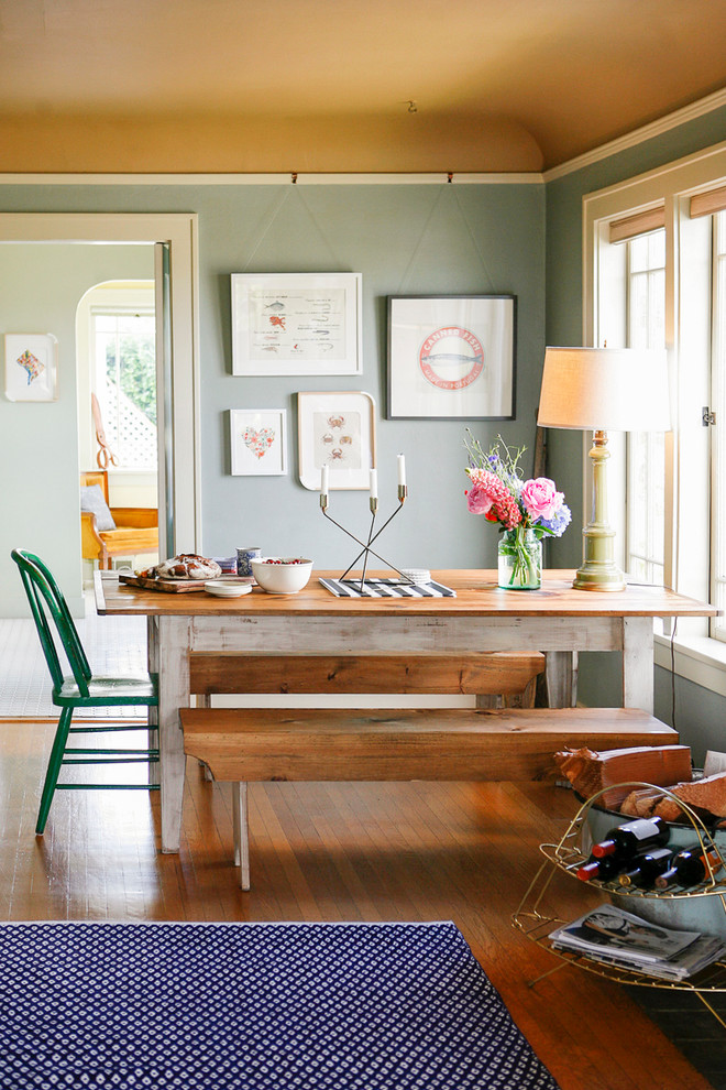 Eclectic medium tone wood floor dining room photo in New York with green walls