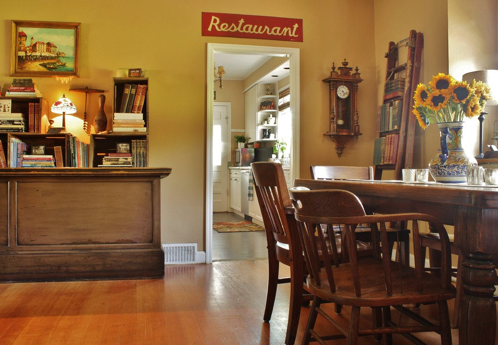 Example of a mid-sized country medium tone wood floor enclosed dining room design in Seattle with beige walls