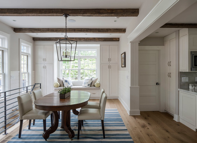 Example of a mid-sized country medium tone wood floor kitchen/dining room combo design in New York with white walls and no fireplace