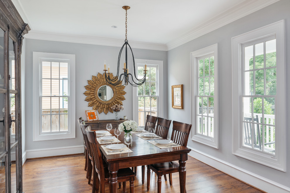 Enclosed dining room - mid-sized transitional medium tone wood floor and brown floor enclosed dining room idea in Houston with blue walls and no fireplace