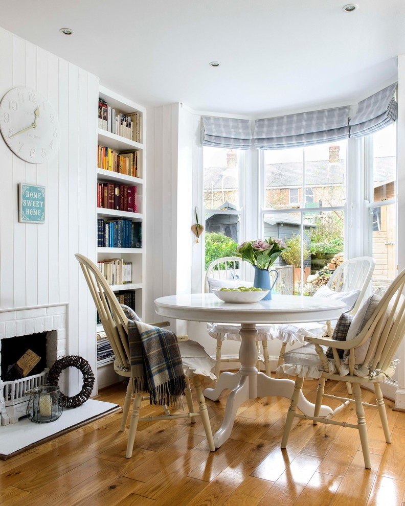Example of a small coastal medium tone wood floor dining room design in Kent with white walls, a standard fireplace and a brick fireplace