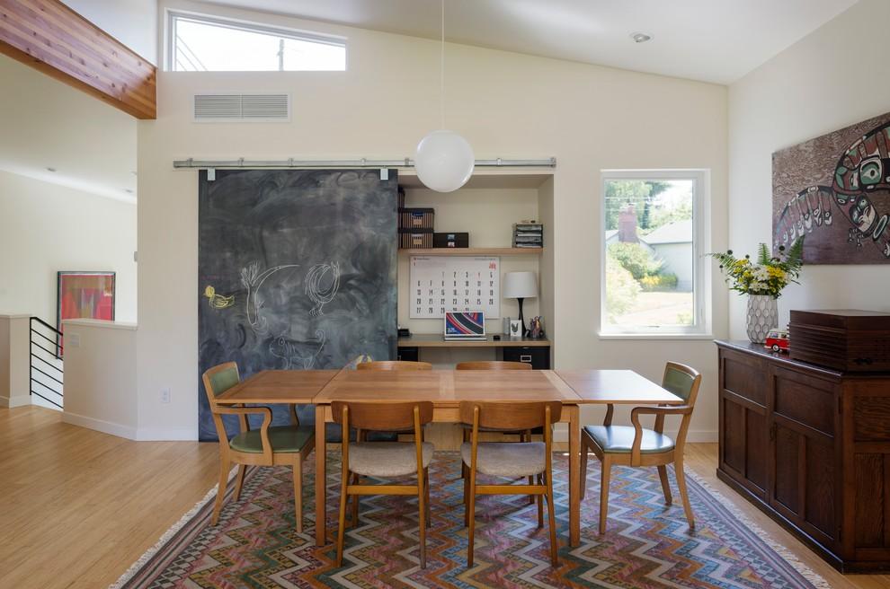 Example of a mid-century modern medium tone wood floor dining room design in Seattle
