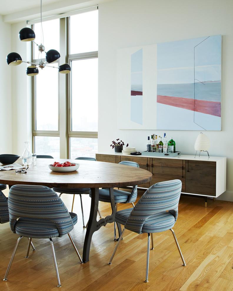 Dining room - scandinavian medium tone wood floor dining room idea in New York with white walls