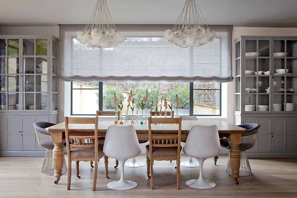 Large trendy light wood floor dining room photo in London with white walls and no fireplace