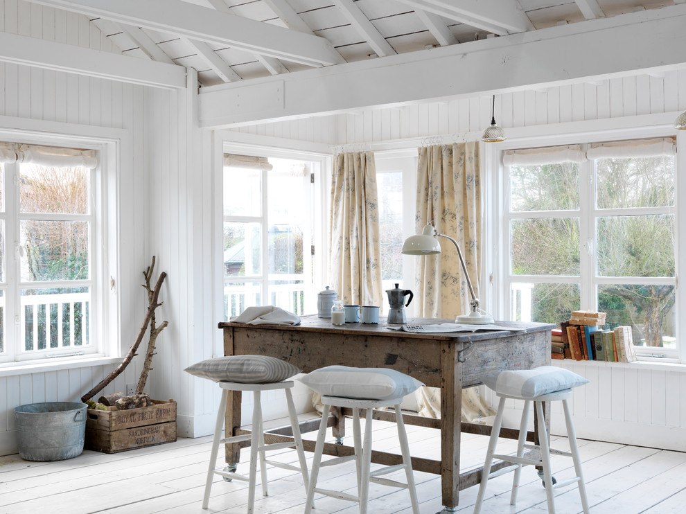 Dining room - coastal light wood floor dining room idea in Sussex with white walls