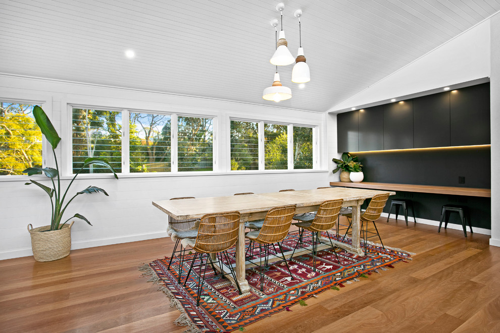 Example of a trendy medium tone wood floor great room design in Sydney with white walls