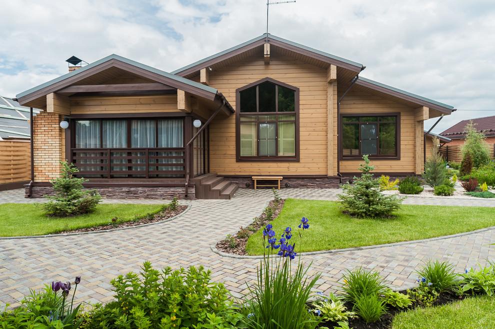 Новый формат декора квартиры: двухэтажный фасад частного дома коричневого цвета в стиле кантри с облицовкой из дерева, двускатной крышей и крышей из гибкой черепицы