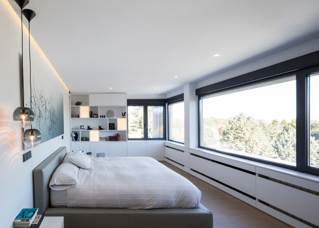 Diseño de dormitorio principal, moderno, grande, sin chimenea, con paredes blancas y suelo de madera en tonos medios