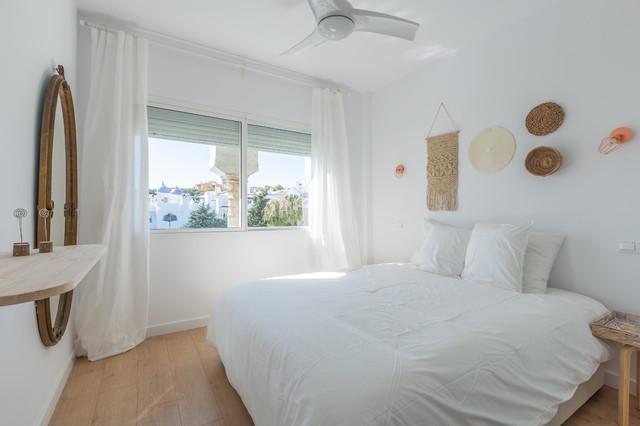 Imagen de dormitorio principal, mediterráneo, de tamaño medio, con paredes blancas, suelo de madera clara y suelo marrón