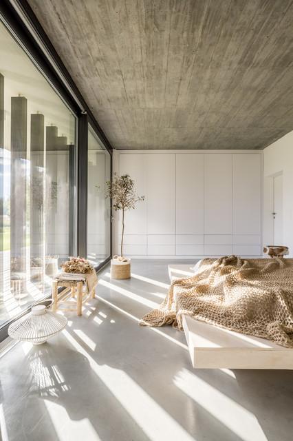 Modelo de dormitorio moderno con paredes blancas, suelo de cemento y suelo gris