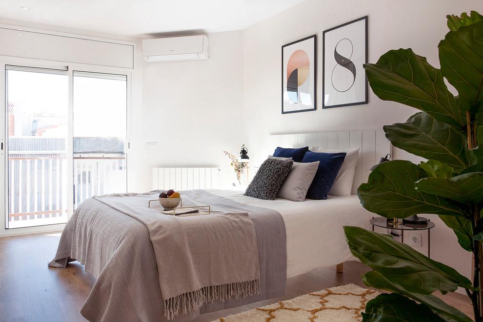 Example of a danish guest medium tone wood floor and brown floor bedroom design in Barcelona with white walls
