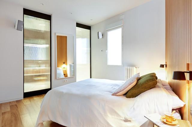 Diseño de dormitorio principal, moderno, grande, sin chimenea, con paredes blancas, suelo de cemento y suelo gris