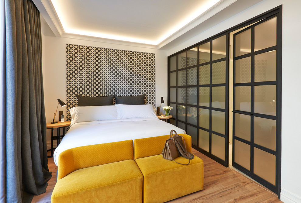 Example of a mid-sized trendy master light wood floor bedroom design in Barcelona with white walls and no fireplace