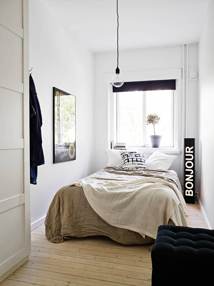 Bedroom - small scandinavian guest light wood floor bedroom idea in Madrid with white walls and no fireplace