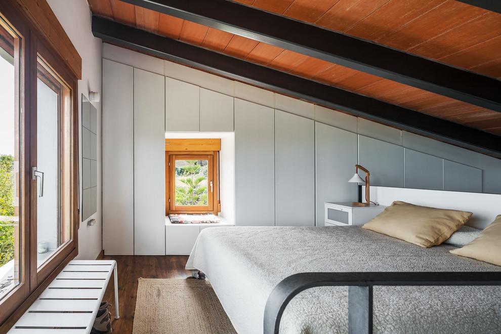 Foto de dormitorio contemporáneo con paredes grises, suelo de madera en tonos medios y suelo marrón