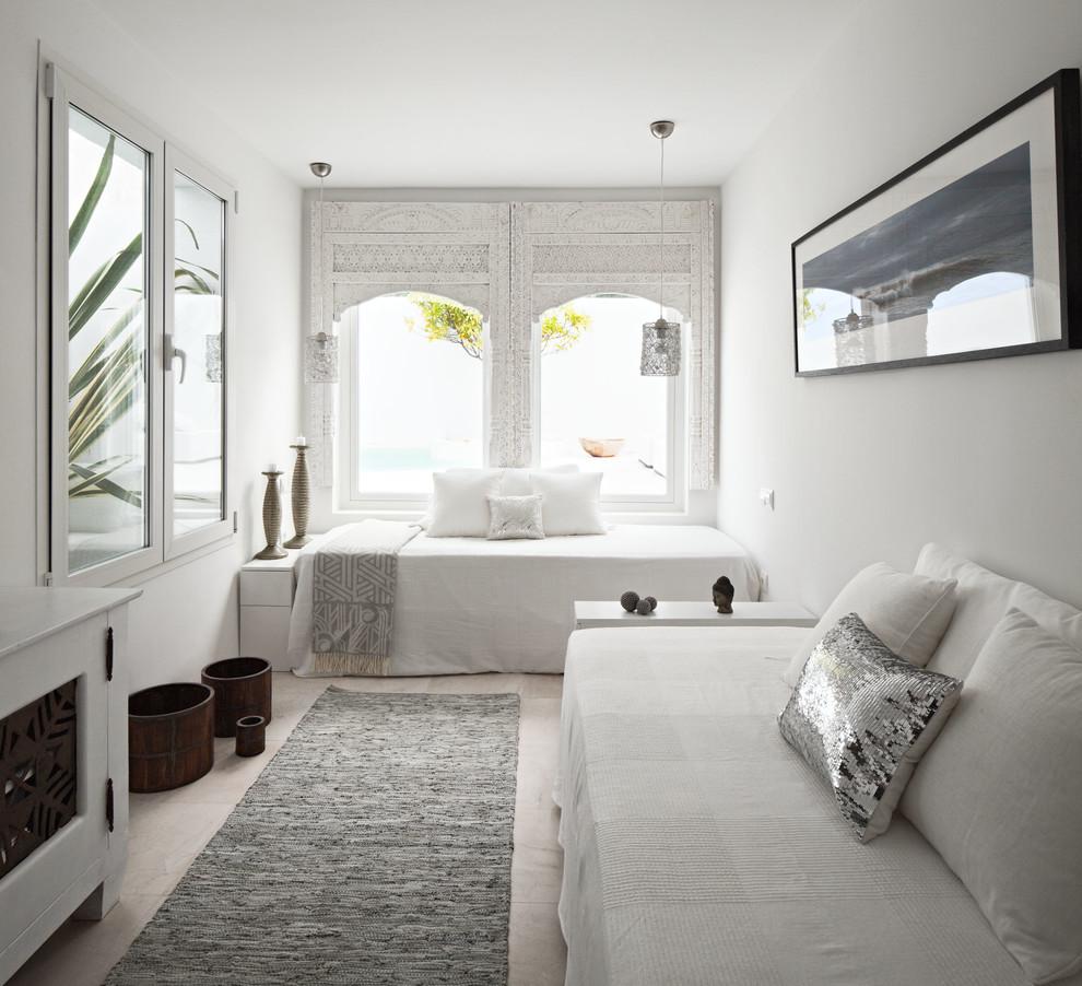 Ejemplo de habitación de invitados mediterránea, de tamaño medio, sin chimenea, con paredes blancas y suelo de travertino