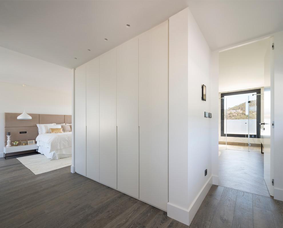 Imagen de dormitorio principal, contemporáneo, extra grande, sin chimenea, con paredes blancas y suelo de madera en tonos medios