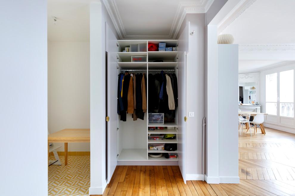 Idées déco pour un petit placard dressing contemporain neutre avec des portes de placard blanches et un sol en bois brun.