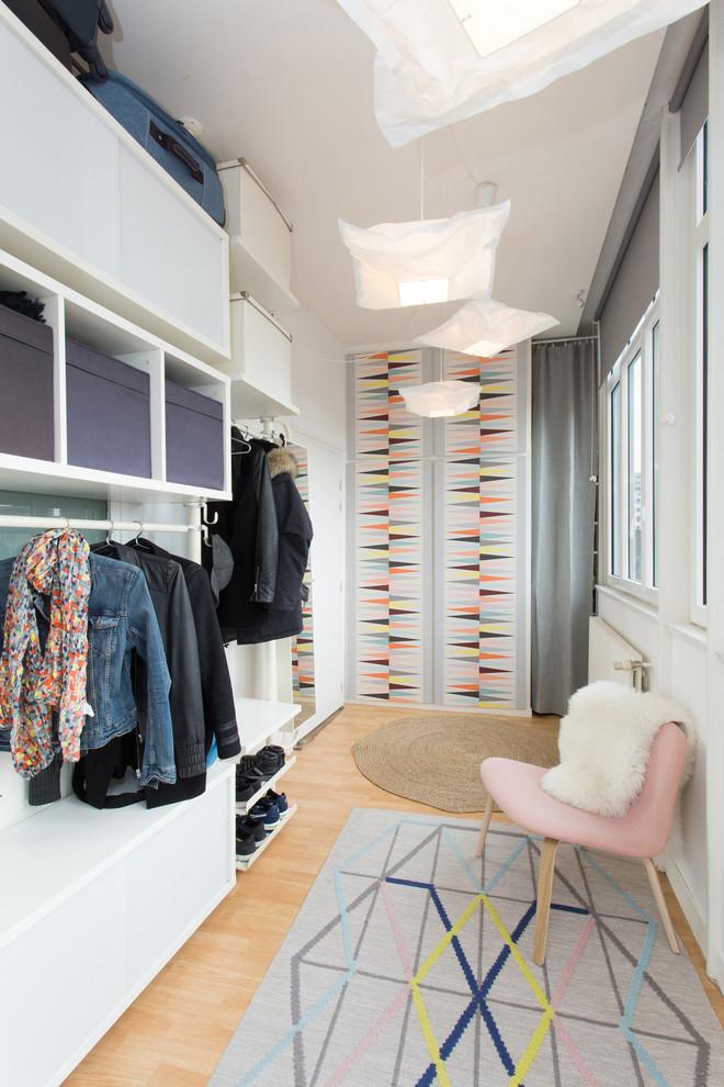 Inspiration pour un dressing room nordique de taille moyenne pour une femme avec des portes de placard blanches, un sol en bois clair et un sol beige.