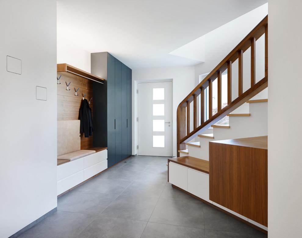 Immagine di un ingresso di medie dimensioni con pareti bianche, una porta singola e una porta bianca