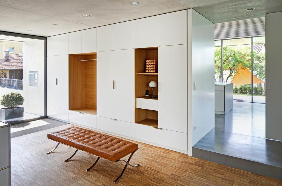 Minimalist medium tone wood floor and brown floor foyer photo in Stuttgart with white walls