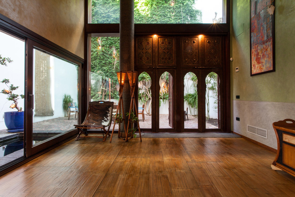 Example of a mid-sized island style medium tone wood floor front door design in Seville with green walls and a dark wood front door