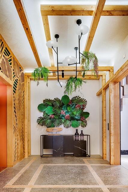 Ejemplo de vestíbulo tropical, grande, con paredes blancas y puerta de madera clara