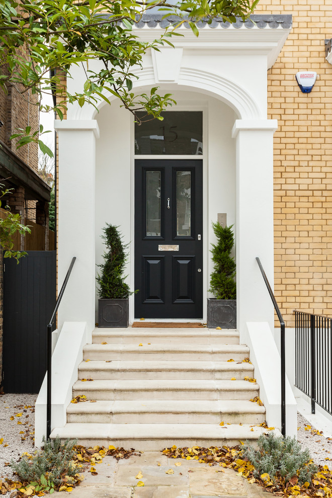 Inspiration for a timeless entryway remodel in London with a black front door