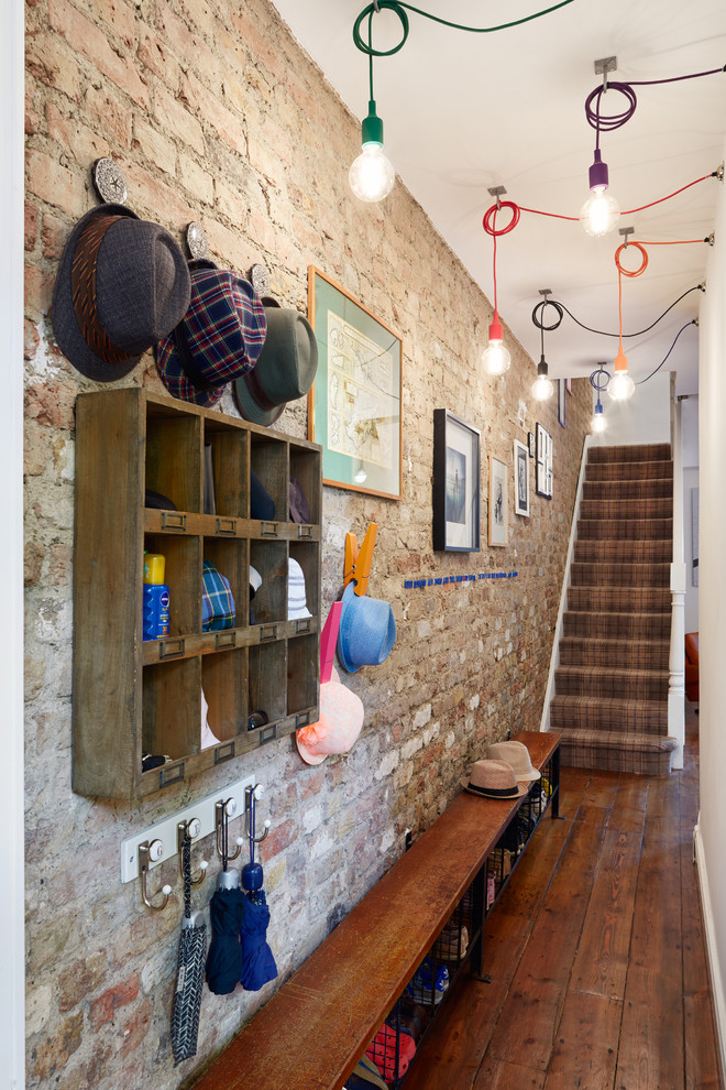 Example of a small eclectic dark wood floor mudroom design in London