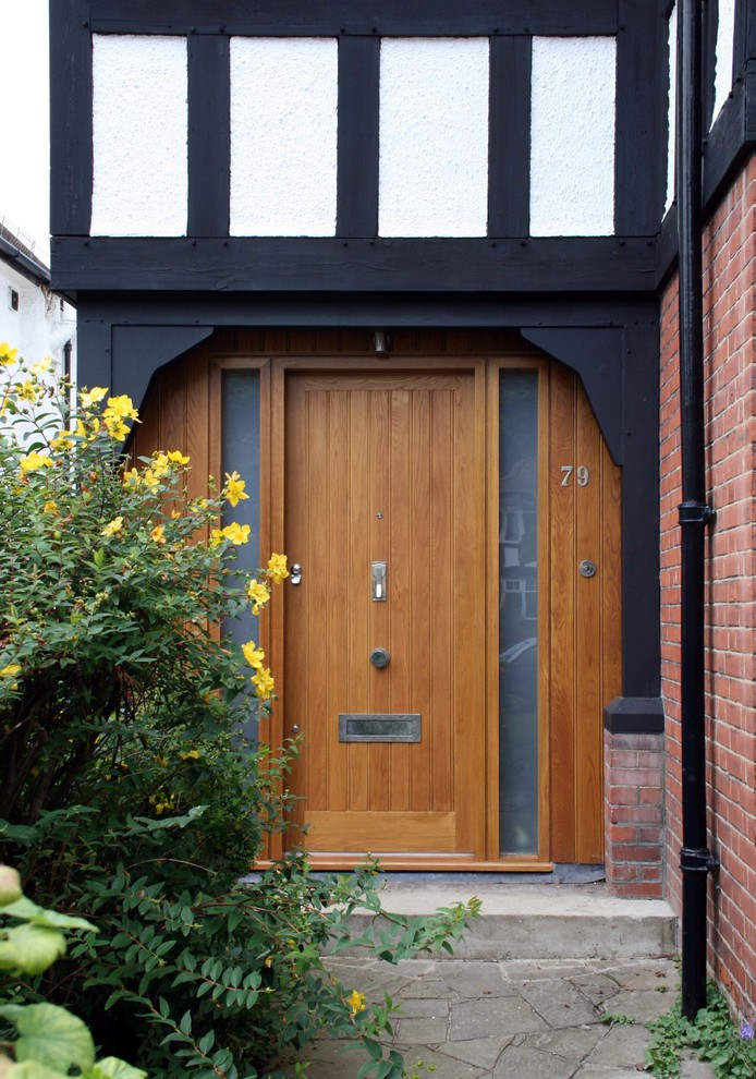 Entryway - contemporary entryway idea in London with a medium wood front door