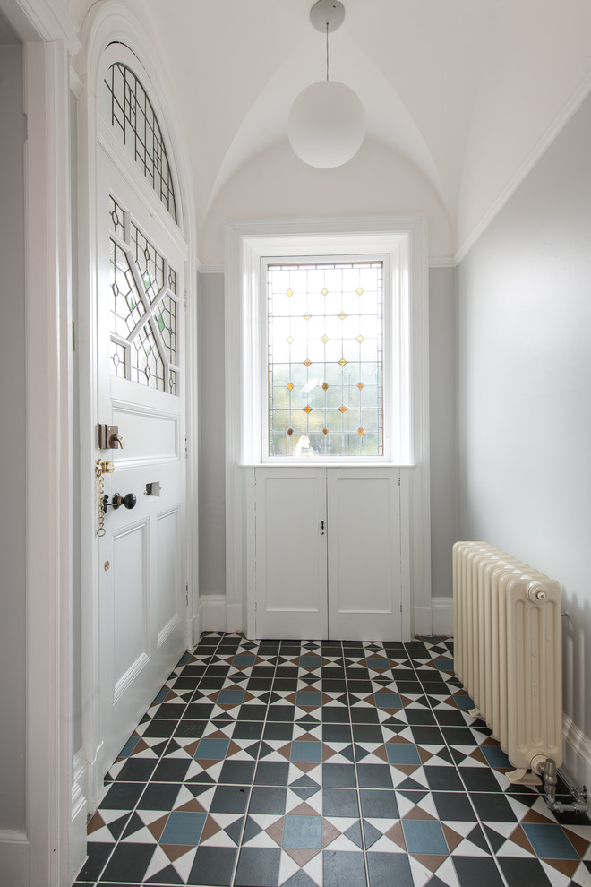 Example of a mid-sized ornate ceramic tile entryway design in Other with gray walls and a white front door