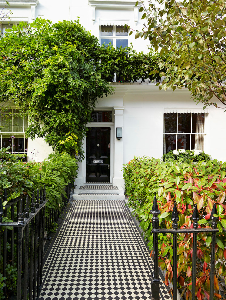 Example of a large classic ceramic tile entryway design in London with a black front door and white walls