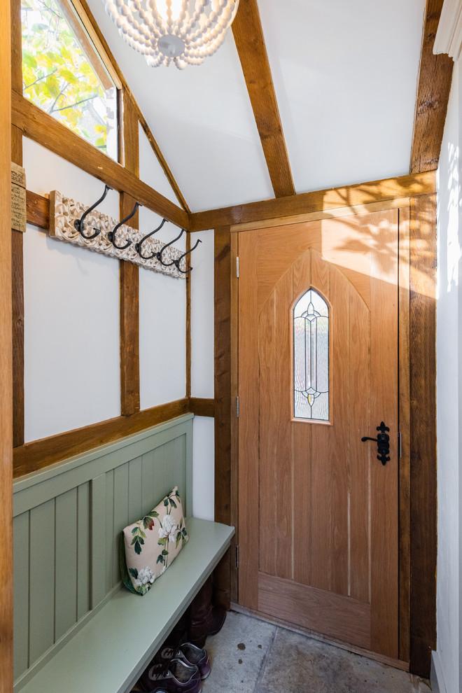 Foto de entrada campestre con paredes blancas, puerta simple, puerta de madera en tonos medios y suelo gris