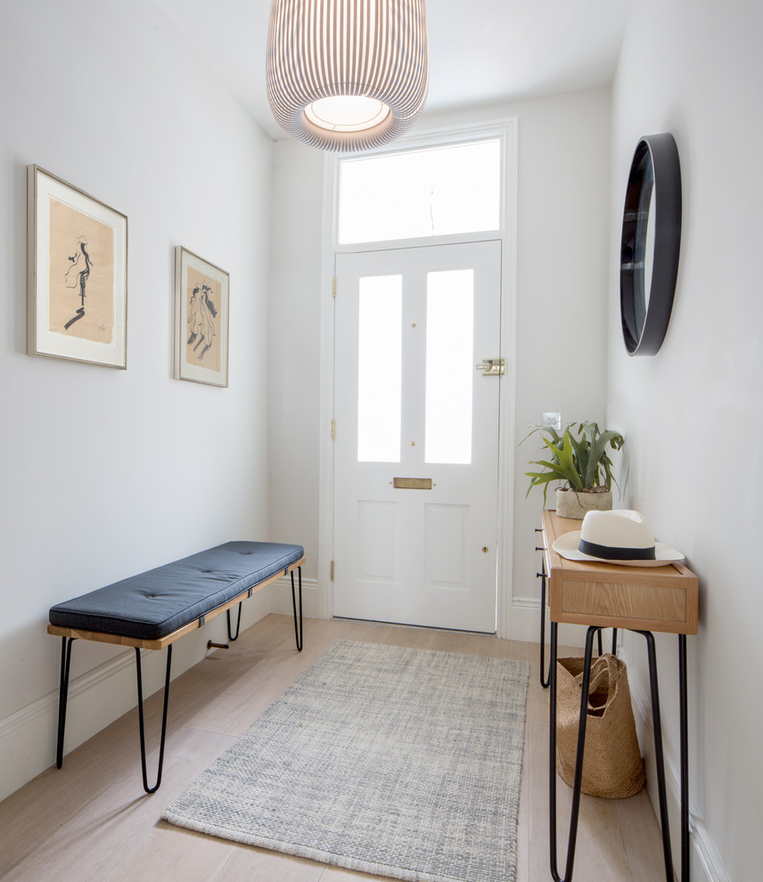 Entryway - mid-sized contemporary light wood floor and beige floor entryway idea in London with gray walls and a white front door