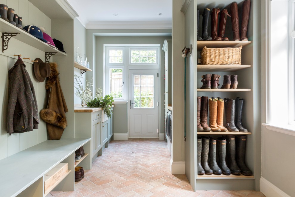 Inspiration for a large timeless brick floor and orange floor mudroom remodel in Surrey with green walls