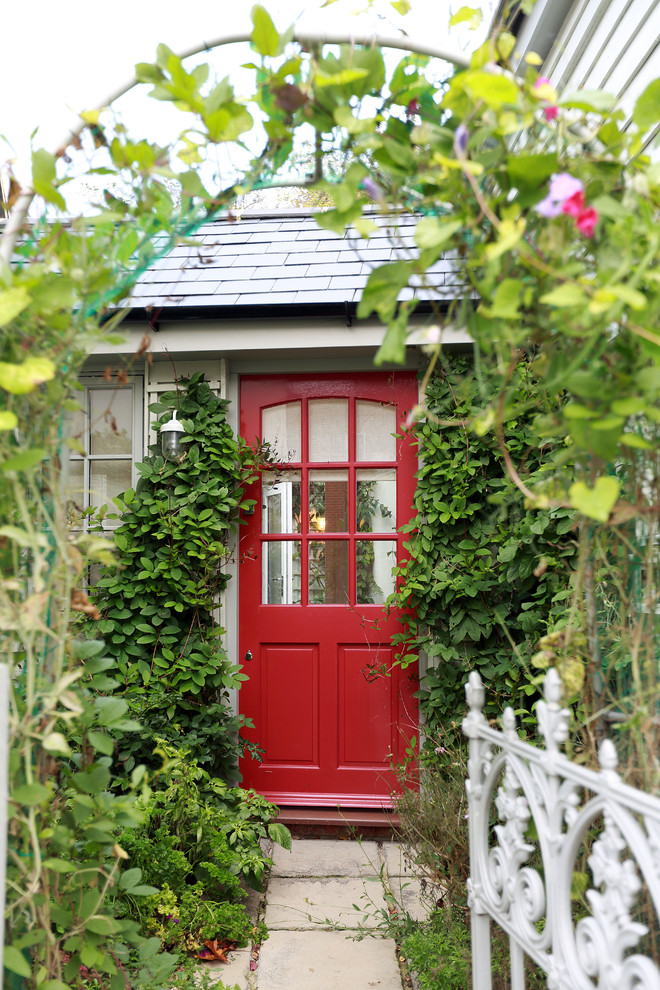 Inspiration for a timeless entryway remodel in London with a red front door