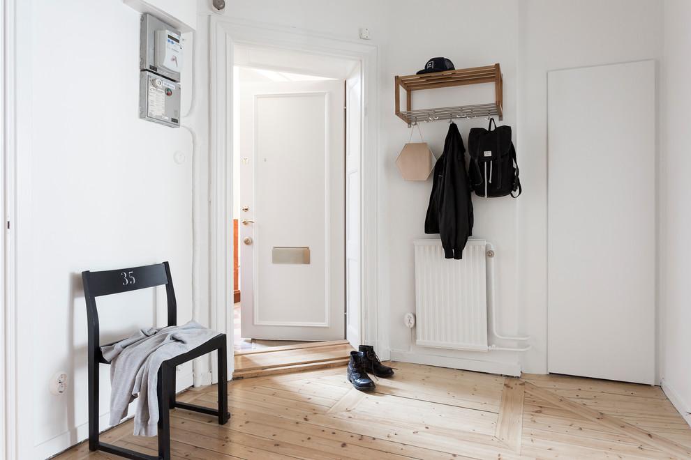 Exempel på en mellanstor minimalistisk farstu, med vita väggar, ljust trägolv, beiget golv, en enkeldörr och en vit dörr