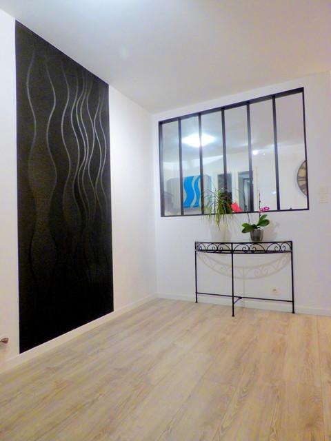 Cette image montre un grand hall d'entrée minimaliste avec un mur noir, sol en stratifié et un sol gris.