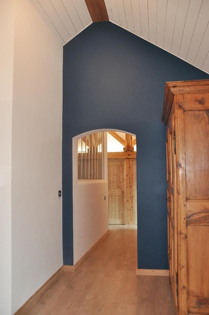 Cette image montre une entrée design avec un mur bleu et un sol en bois clair.