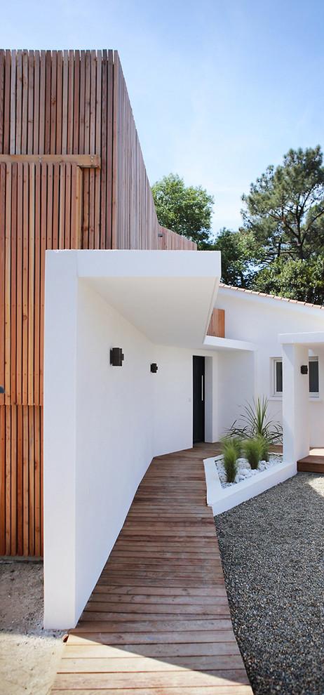 Idées déco pour une porte d'entrée contemporaine avec un mur blanc, un sol en bois brun, une porte simple, une porte noire et un sol marron.