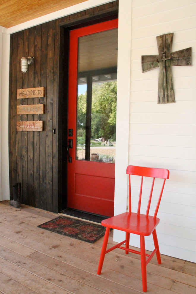 Mid-sized farmhouse medium tone wood floor entryway photo in Austin with a red front door and white walls