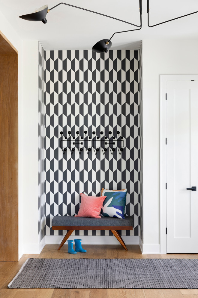 Inspiration for a large contemporary light wood floor, brown floor and wallpaper foyer remodel in Minneapolis with white walls
