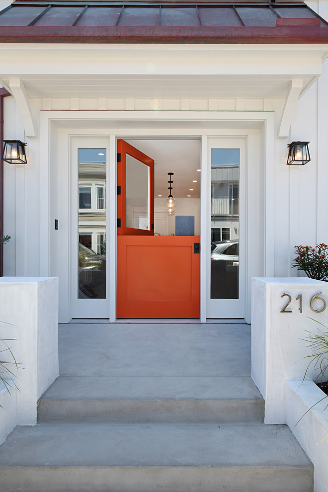 Mid-sized beach style concrete floor and gray floor entryway photo in Orange County with an orange front door and white walls