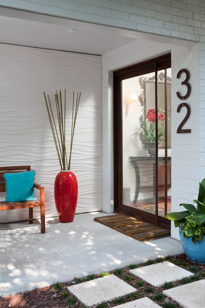 Example of a trendy single front door design in Wilmington with white walls and a glass front door