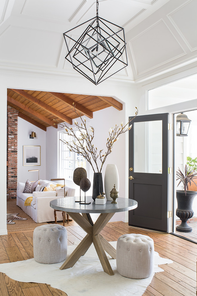 Example of a mid-sized transitional light wood floor and brown floor entryway design in Los Angeles with white walls and a black front door