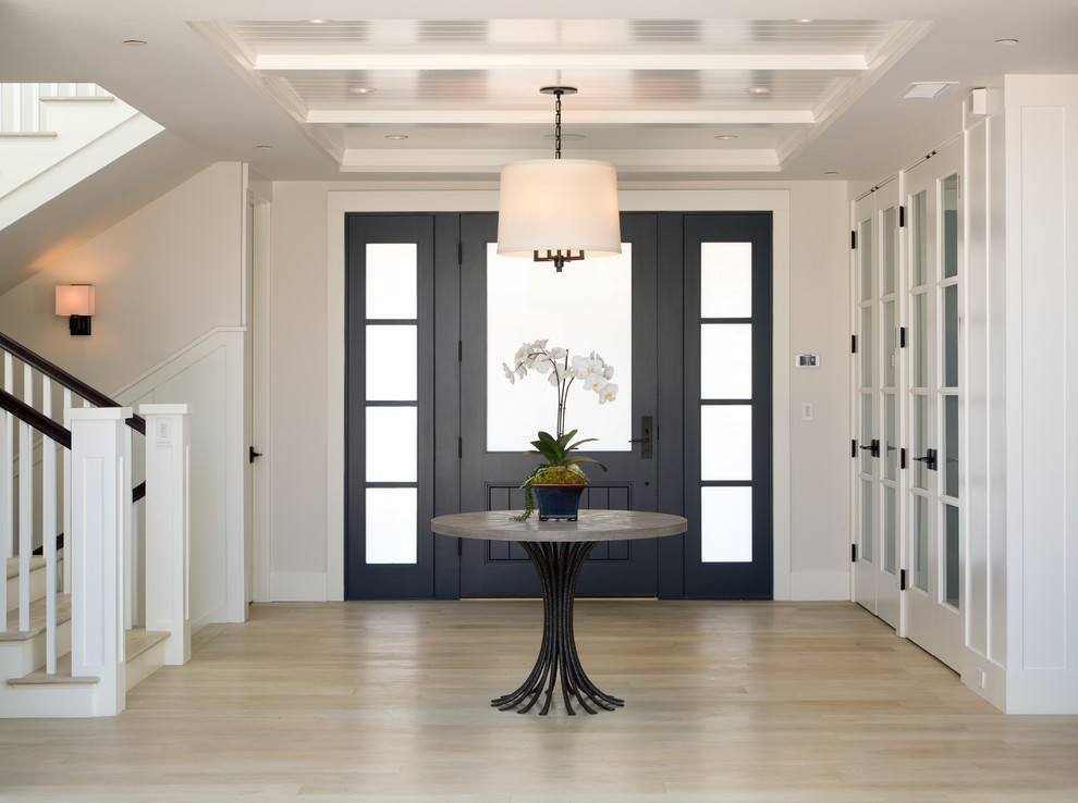 Large transitional light wood floor and beige floor entryway photo in San Diego with a black front door and white walls