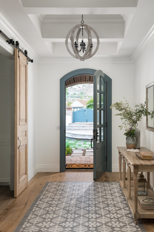 Example of a cottage light wood floor and beige floor entryway design in Phoenix with white walls and a blue front door