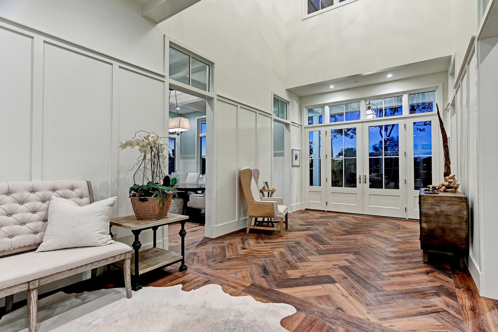 Entryway - huge country medium tone wood floor and brown floor entryway idea in Los Angeles with white walls and a gray front door